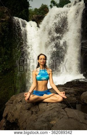 Young Caucasian Woman Sitting On The Rock, Meditating, Practicing Yoga And Pranayama. Hands In Gyan