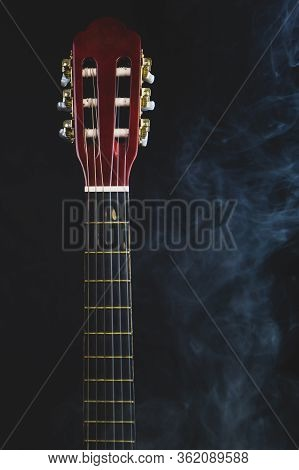 Guitar In Smoke On The Black Background. Acoustic Musical Instrument. Strings On The Guitar Neck
