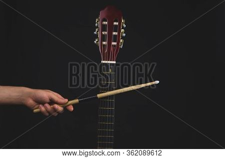 Drumstick In The Hand And Guitar Fretboard Close Up. Acoustic Musical Instrument. Copy Space