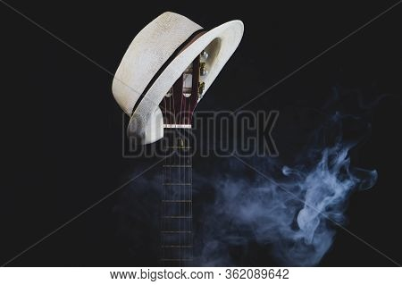 White Hat Hangs On The Smoking Guitar Fretboard. Acoustic Musical Instrument. Strings On The Guitar