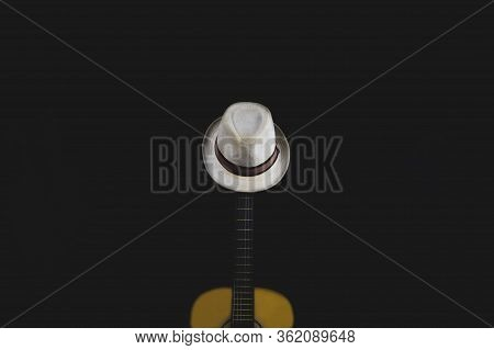 White Hat Hangs On The Guitar Fretboard. Acoustic Musical Instrument. Strings On The Guitar Neck Clo