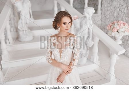 A Beautiful Girl Is Standing In A Wedding Dress. Photoshoot In White. Stylish Photo Shoot Of The Bri