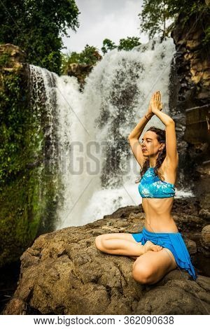 Young Caucasian Woman Sitting On The Rock, Meditating, Practicing Yoga And Pranayama. Hands In Namas