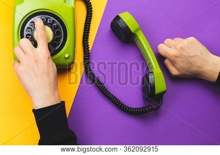 Hand Dialing A Number On A Classic Phone With Round Dial. Vintage Green Telephone With Handset On Co