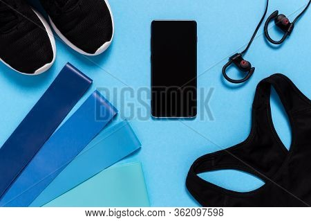 Flat Lay Of Sports Bra, Running Shoes, Mobile Phone And Resistance Bands On Blue Background. Sports