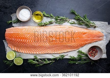 Fresh Raw Salmon Or Trout Sea Fish Fillet With And Herbs On Black Background, Top View