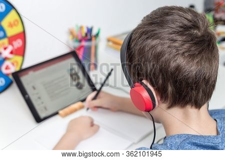 Eight Years Old Boy Behind The Table Study At Home Using A Tablet And Headphones, Digital Education,