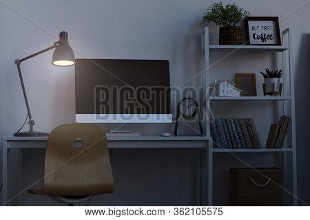 Background Image Of Home Office Workplace At Night, With Focus On Computer Desk Lit By Dim Lamp Ligh