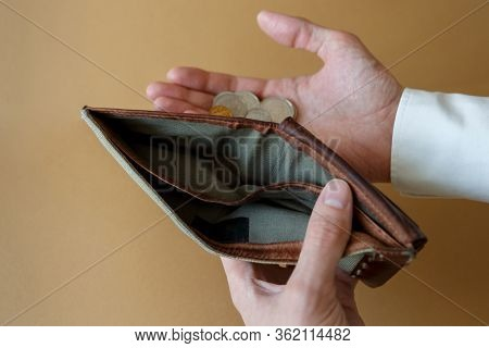 Empty Wallet In The Hands Of A Man On A Light Solid Background, Top View. Bankruptcy And Insolvency