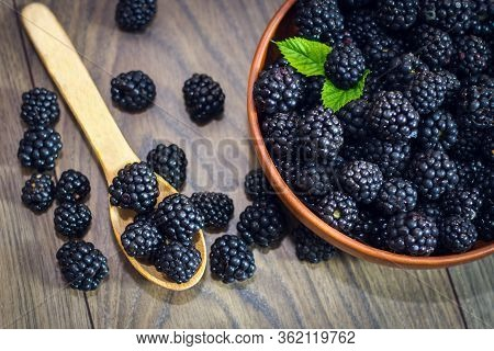 Ripe Blackberries With Leaves In A Clay Bowl On A Light Wooden Background. Flat Lay, Top View. Photo