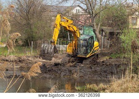 Crawler Excavator Or Digger Dredges On The Lake