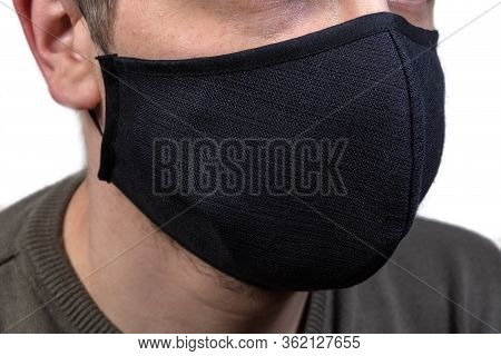 Black Protective Fabric Mask With Rubber Bands Wearing On A Face Close-up