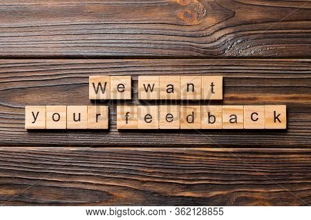 We Want Your Feedback Word Written On Wood Block. We Want Your Feedback Text On Wooden Table For You