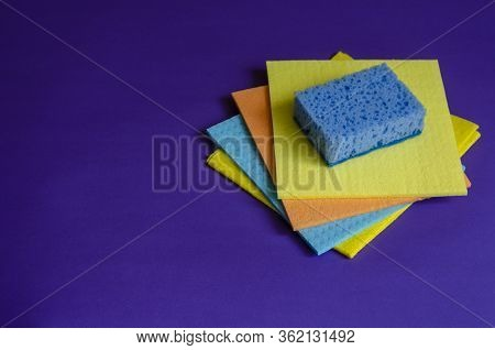 Kitchen Napkins And Sponge On A Blue Background. Four Multi-colored Cleaning Napkins And A Blue Kitc
