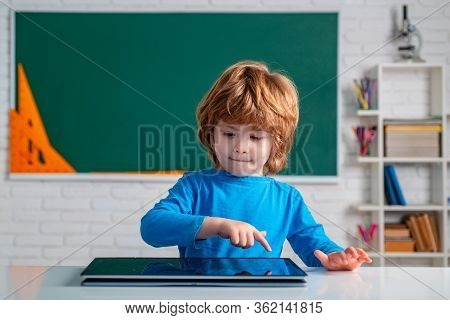 Pupil With Digital Tablet In School Classroom. Pupil In Class Using Digital Tablet. Cute Little Pres