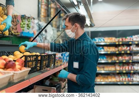 Seller In A Protective Mask Standing In Front Of The Counter With Fruit.