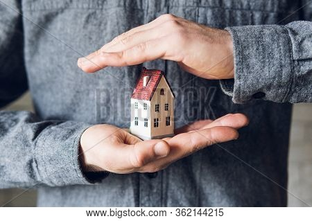 Male Hands Holding And Protecting A Small Toy House. Conceptual Image Of Insurance And Staying Home