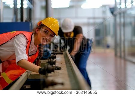 Beautiful Worker Or Technician Or Engineer Woman Smile And Look Forward In Front Of Rail Of The Mach