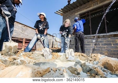 Diverse Community Outreach Program Mixing Cement For Building A Small Affordable House