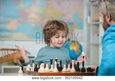 Happy Child And Childhood. Boy Kid Playing Chess At Home. Concentrated Boy Developing Chess Strategy