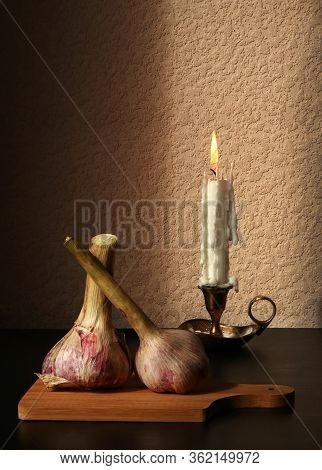 Two Garlic Bulbs On Wooden Cutting Board And Candlestick With Burning Candle Against A Low Key Backg