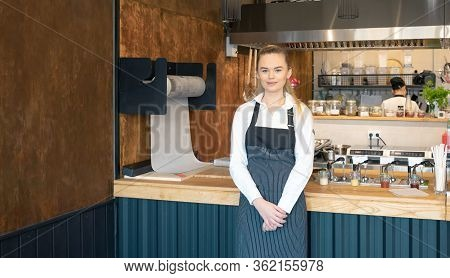 Young Waitress Wearing Apron Posing In Restaurant. Portrait Of A Young Woman On Her First Day Job In
