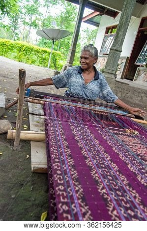 Maumere, West Nusa Tenggara / Indonesia - January 13 2015: Elderly Indonesian Lady Works On The Loom
