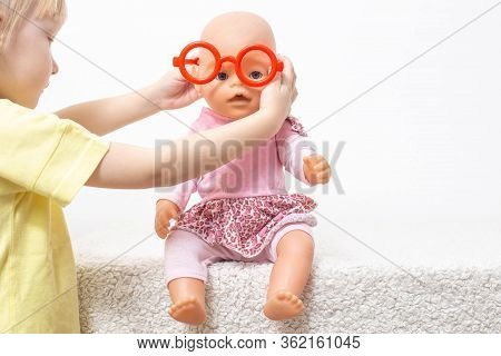 The Child Plays With A Doll And Puts On Toy Glasses. The Concept Of Pediatric Ophthalmology, Selecti