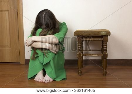 A Beautiful Young Girl Is Sitting On The Floor Near The Door, Victim Wrapped Her Arms Around Her Kne