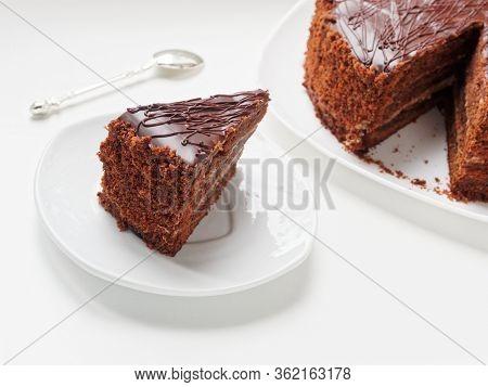Chocolate Cake Prague. Cake With Chocolate Icing. A Piece Of Cake On A Plate Near The Cake.