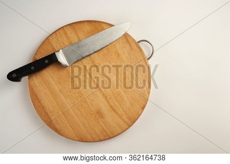 Wooden bread cutting board with stainless steel knife isolated white