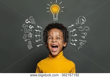 Ideas And Brainstorm Concept. Happy Child School Student With Lightbulb And Chalk Question Marks