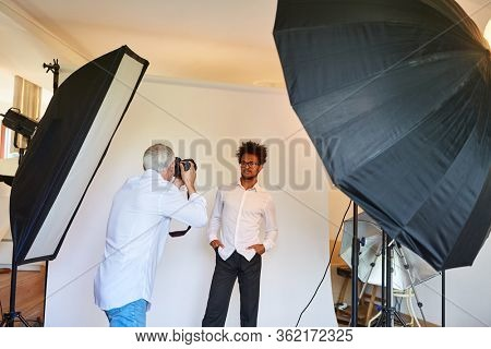 Portrait photographer in the photo studio makes portrait photos of model in cool pose