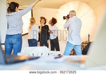 Photo assistant and make-up artist in the styling and make-up of a model