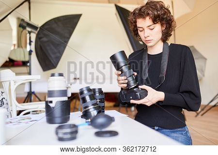 Professional photographer changes lens of SLR camera