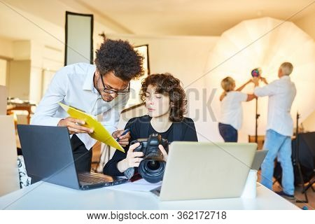 Photo assistant with clipboard and photographer with camera in the photo studio