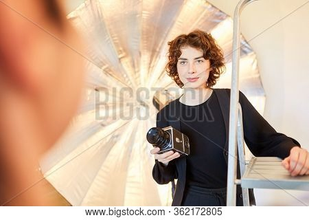 Young photographer with medium format camera in the photo studio during the photo shoot