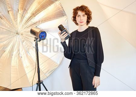 Young woman with medium format camera in front of a flash unit in the photo studio