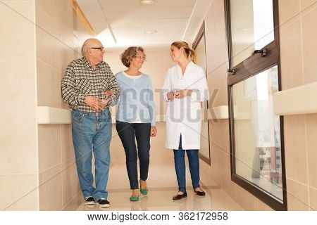 Senior couple as visitors in nursing home in conversation with a geriatric nurse
