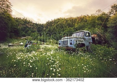 Old Blue Rusty Broken Truck Abandoned In The Middle Of Spring Green Rural Field Surrounded By Trees.