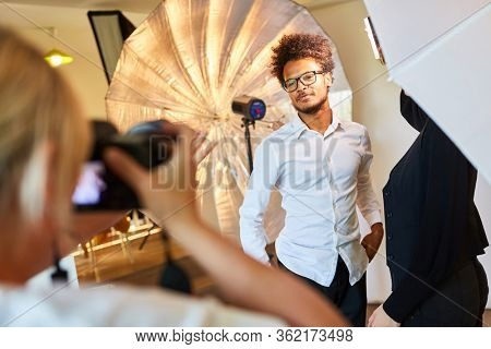 Young man posing as a model for portrait photos during the photo shoot in the studio