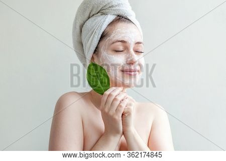 Minimal Beauty Portrait Woman Girl In Towel On Head Applying White Nourishing Mask Or Creme On Face,