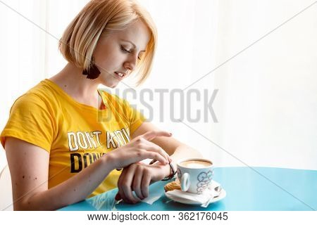 Beautiful, Young Girl In Yellow T-shirt Looking At Her Wristwatch. Waiting For Someone. Inside A Cof