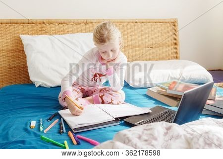 Caucasian Girl Child Sitting In Bed And Learning Online On Laptop Internet. Virtual Class Lesson Sch
