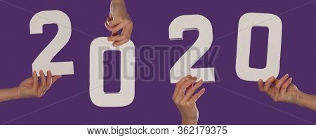 Female hand holding up the number 2 against a purple background conceptual of numbers, measurement, amount, quantity, accounting and mathematics