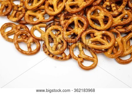 Salty Cracker Cookies In The Shape Of A Pretzel Sprinkled On A White Background. Oktoberfest Symbol