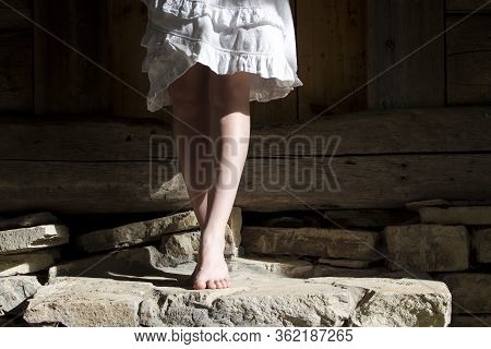 The Legs Of A Girl In A White Dress That Stands On Tiptoe Barefoot On Old Stone Steps