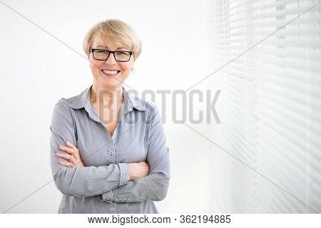Portrait of mature business woman against a window.