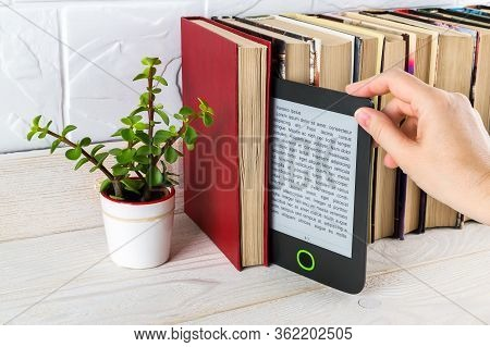 Woman Hand Takes E-reader From Shelf With Paper Books And Small Potted Plant. Copy Space On E-book D