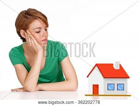 Young woman looks a little house model on white background.